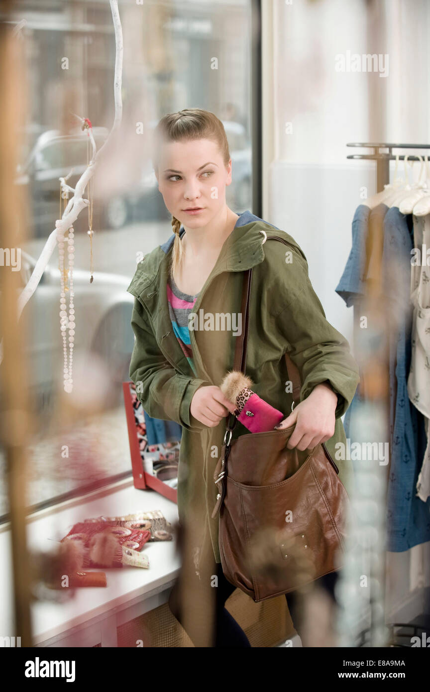 Young woman stealing something in fashion store - Stock Image