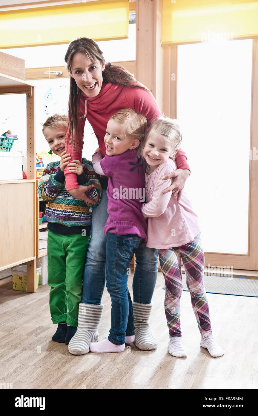 Group picture of female educator and three kids standing in kindergarten - Stock Image