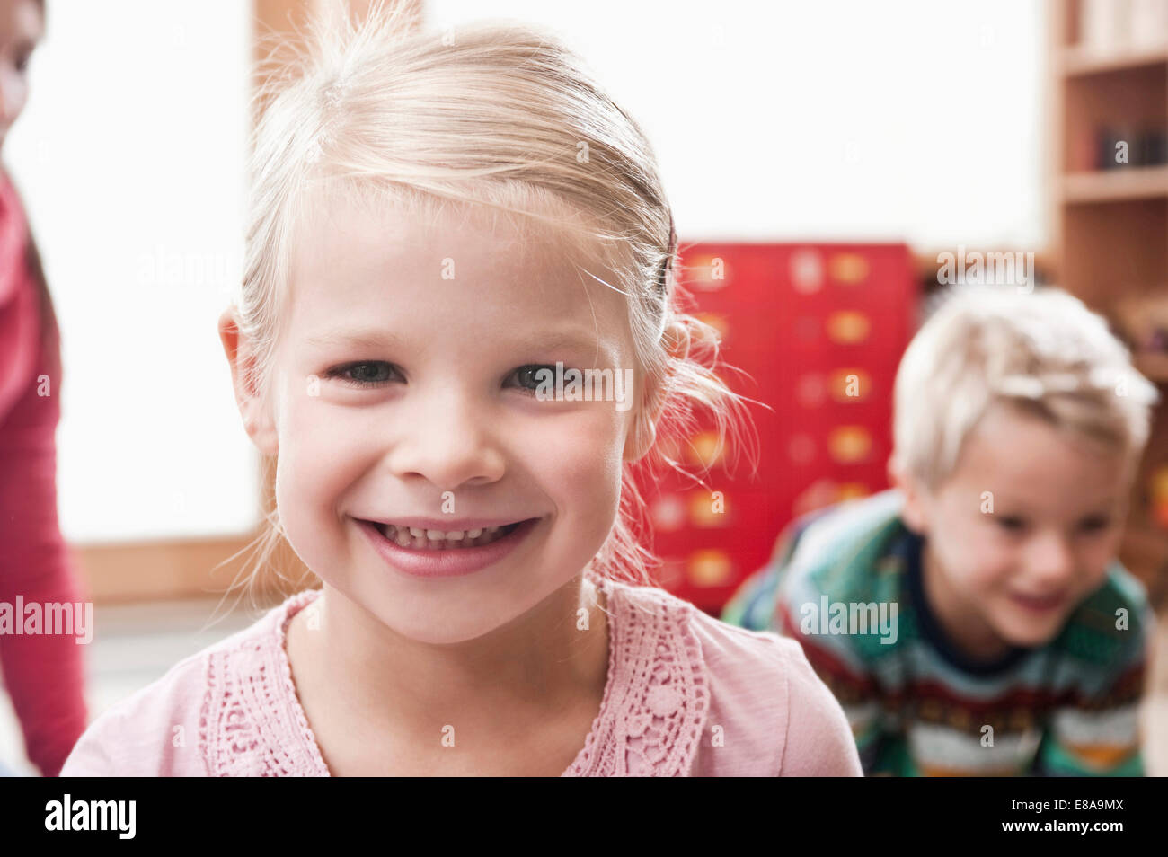 Portrait of smiling little girl in kindergarten - Stock Image