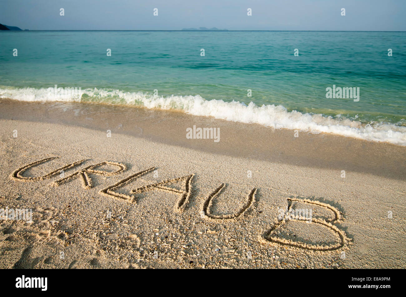 the word 'Urlaub' scratched into sand at beach, Koh Lipe, Thailand - Stock Image