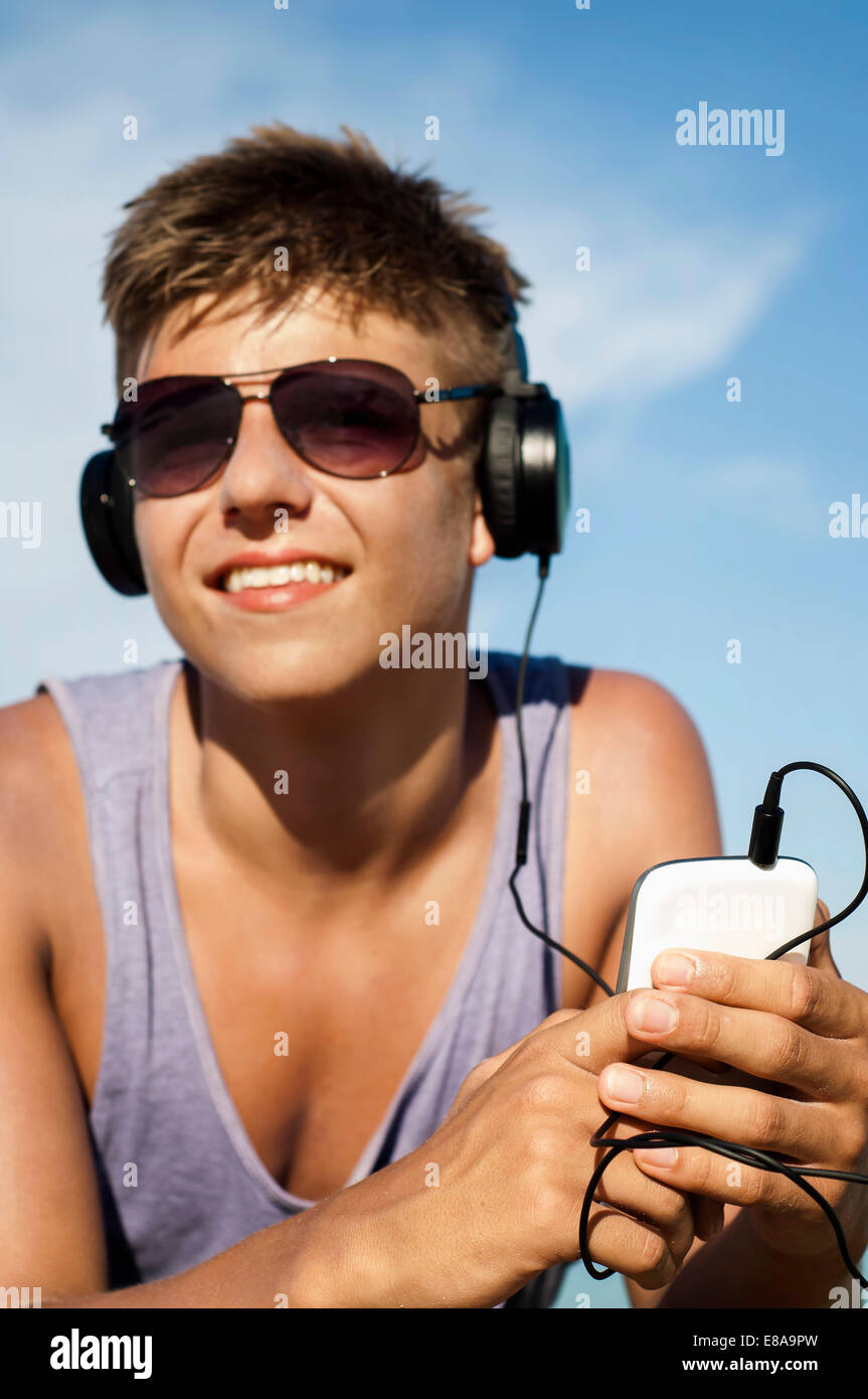 Portrait of teenage boy hearing music at beach, Koh Lipe, Thailand - Stock Image
