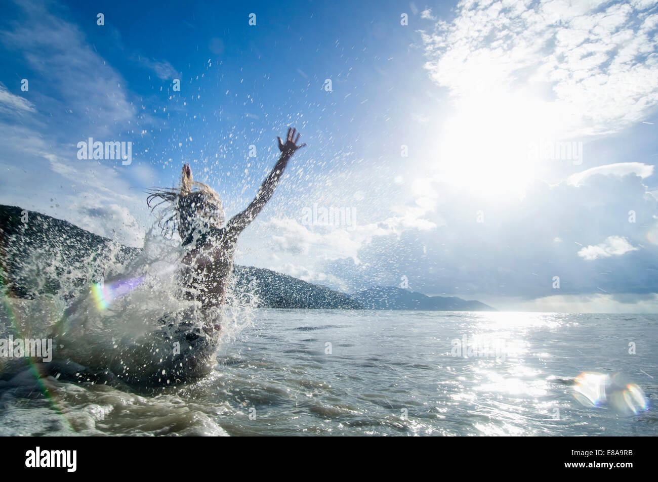 woman jumping into the ocean, Penang, Malaysia - Stock Image