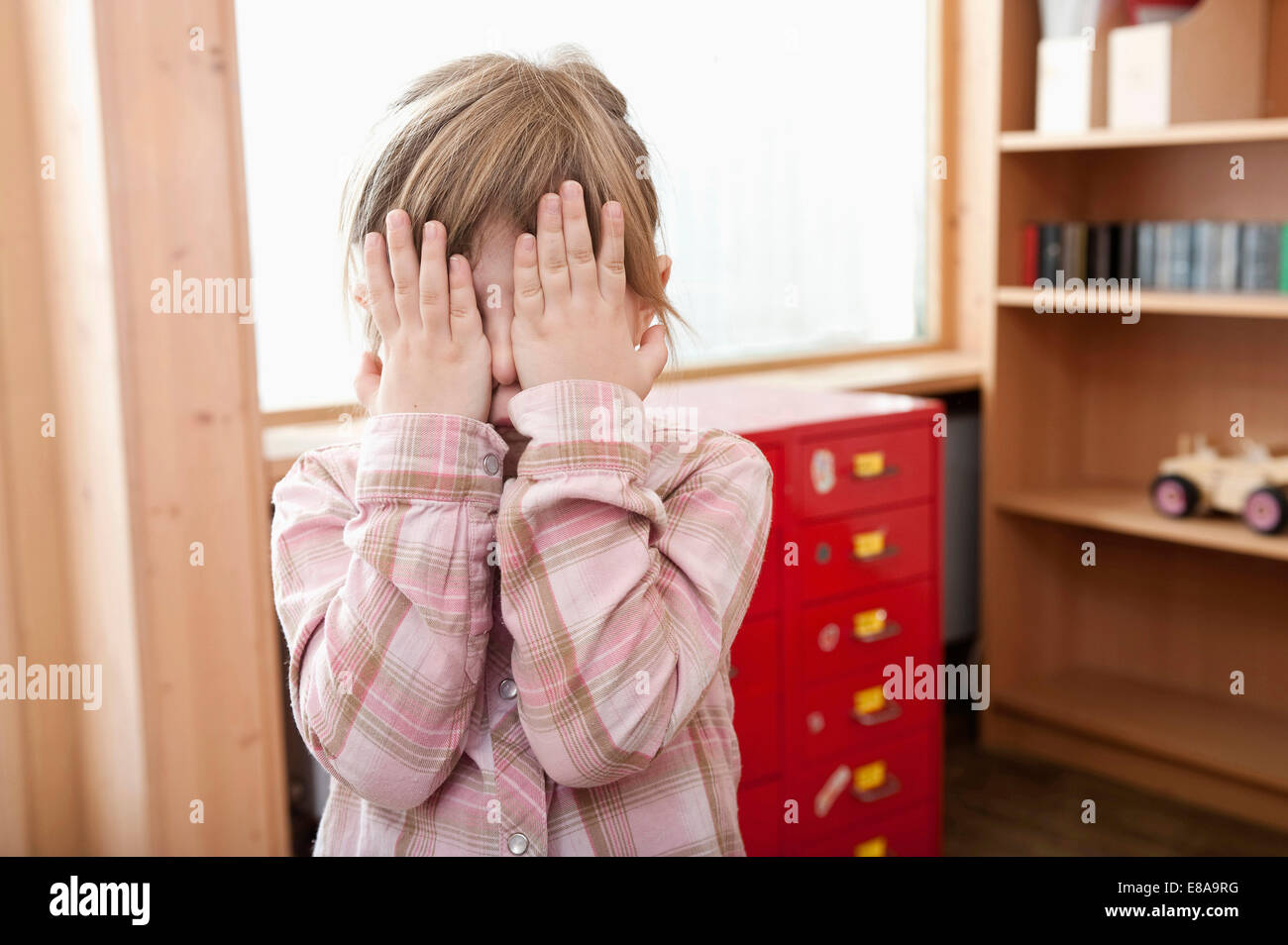 Little girl covering her face with her hands - Stock Image