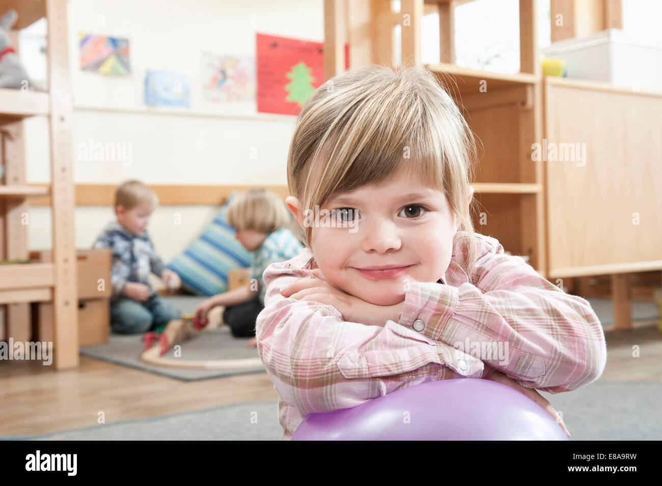 Portrait of smiling little girl with crossed arms - Stock Image