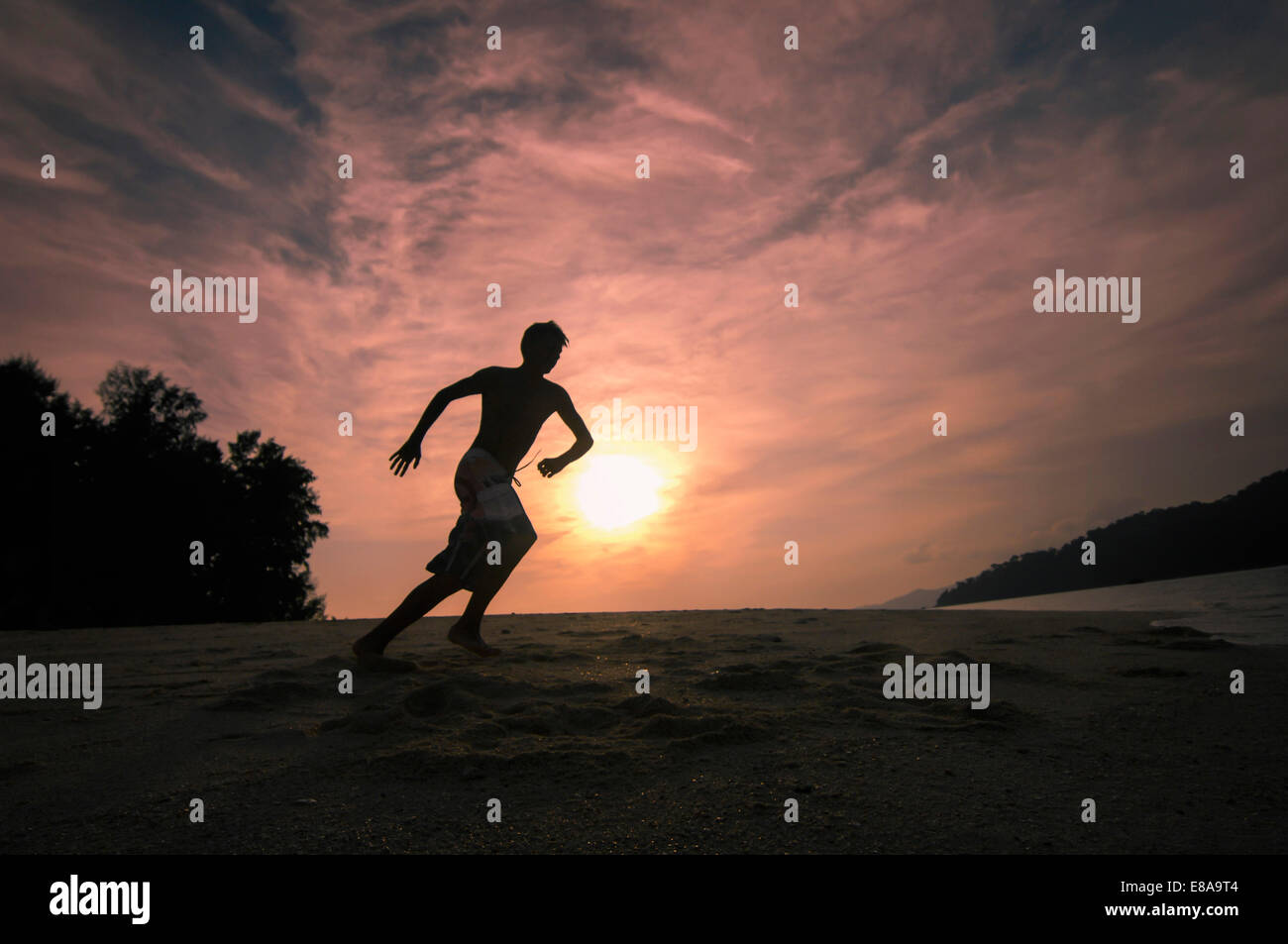 boy running at the beach at sunset, Koh Lipe, Thailand - Stock Image
