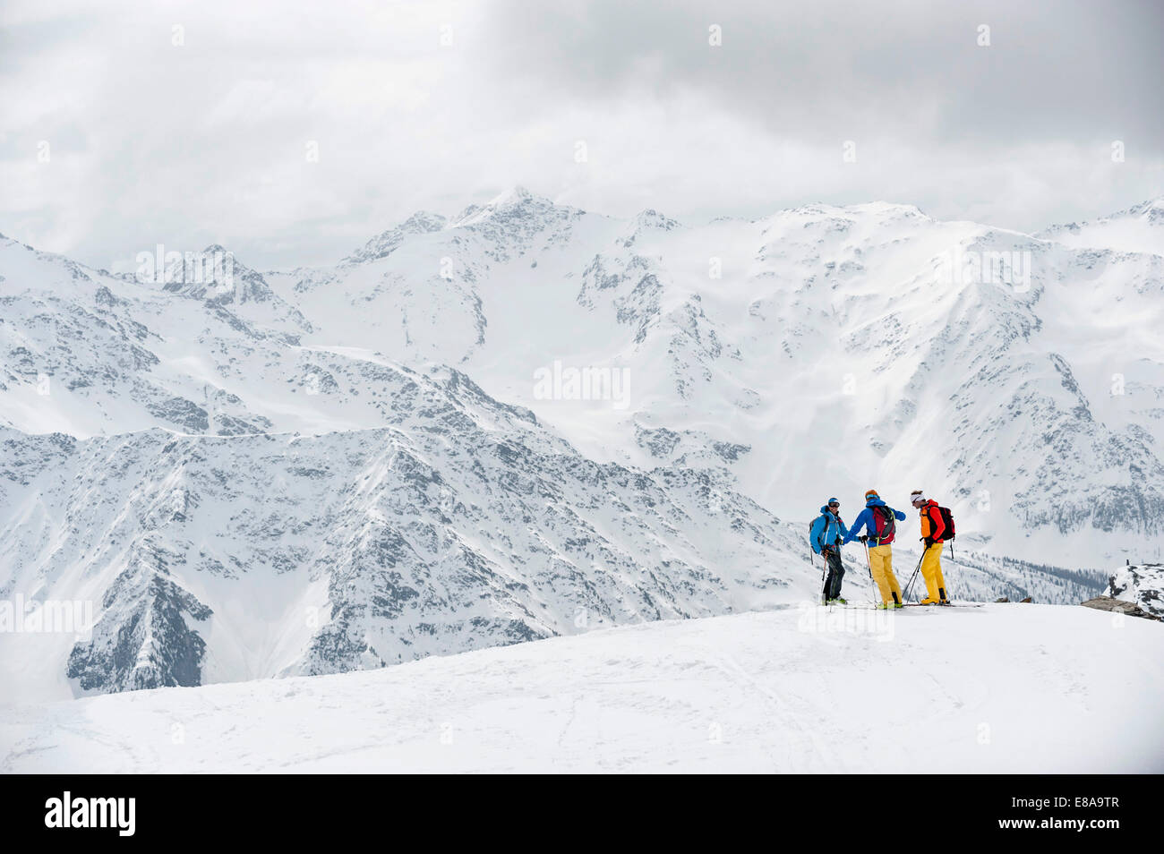 Alps winter mountains three skiers snow - Stock Image