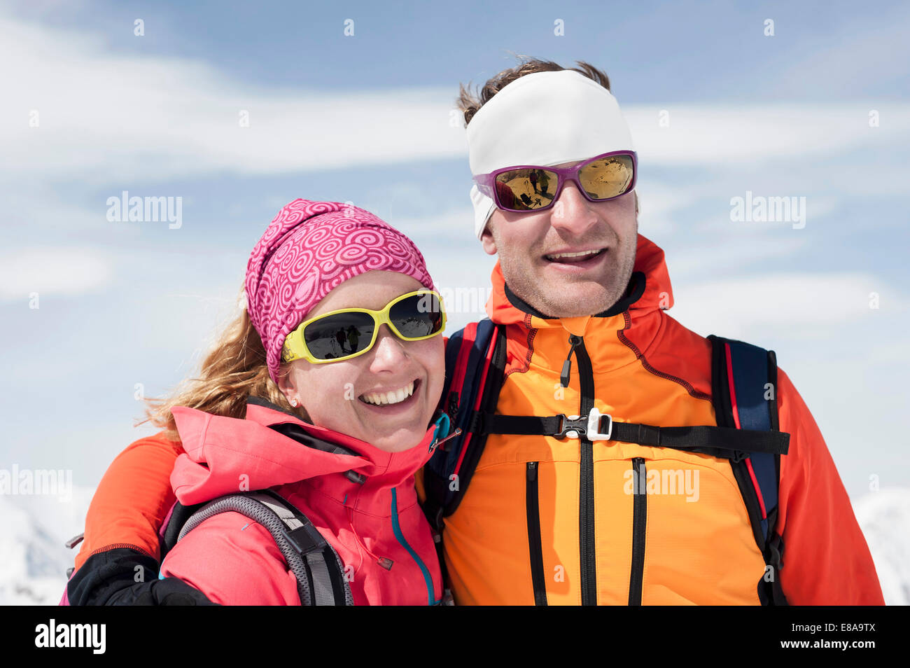 Portrait couple in winter ski suit goggle smiling - Stock Image