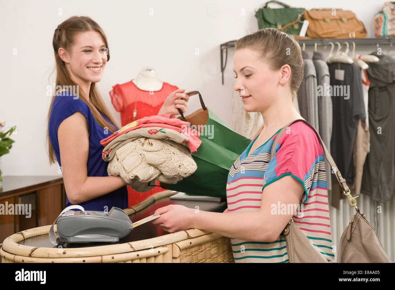 Sales girl with customer at cashpoint - Stock Image