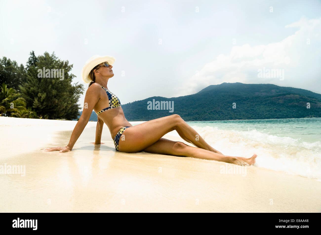 woman sitting on the beach, Koh Lipe, Thailand - Stock Image