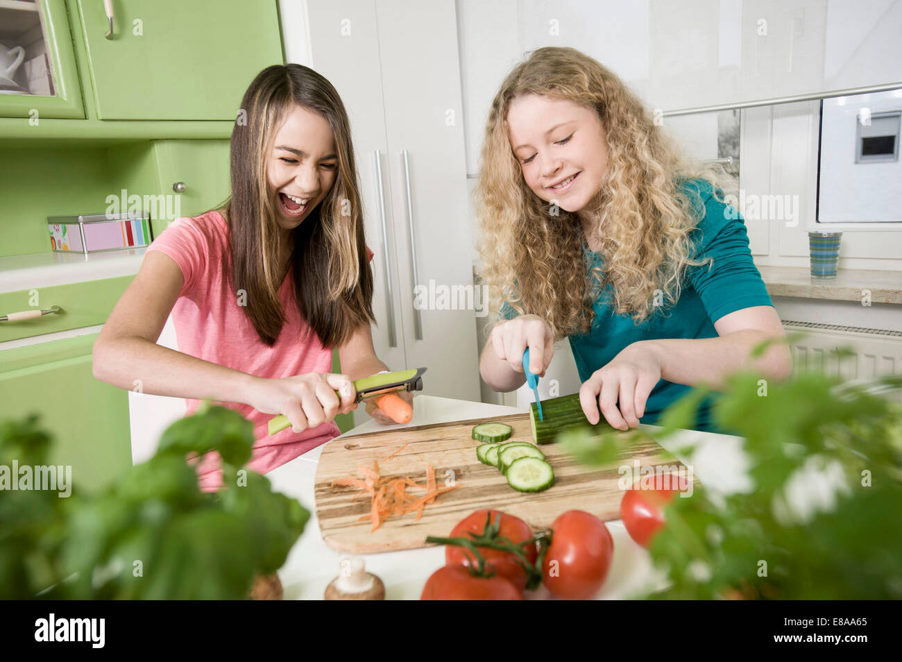 Girls in kitchen chopping vegetables - Stock Image