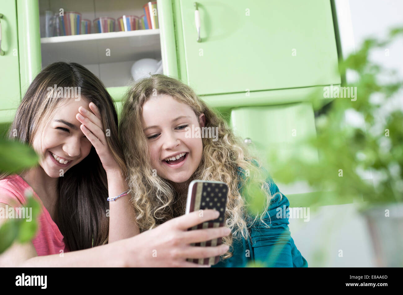 Girls in kitchen with smart phone - Stock Image