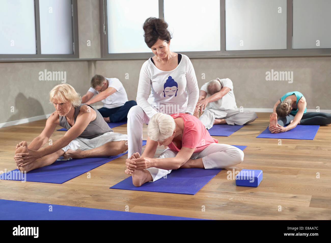 Woman Trainer Teaching Group Yoga Exercises