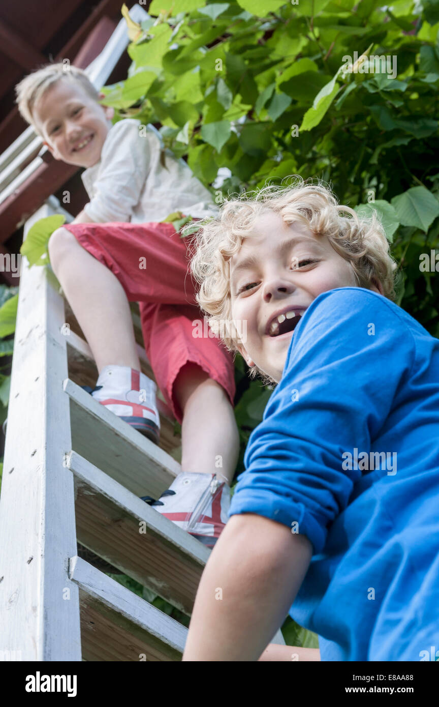 Young boys friends climbing ladder tree-house - Stock Image