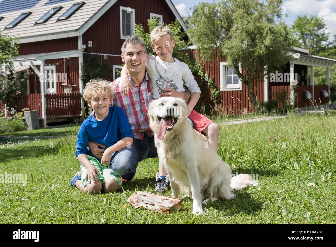 Young family father sons pet dog garden - Stock Image
