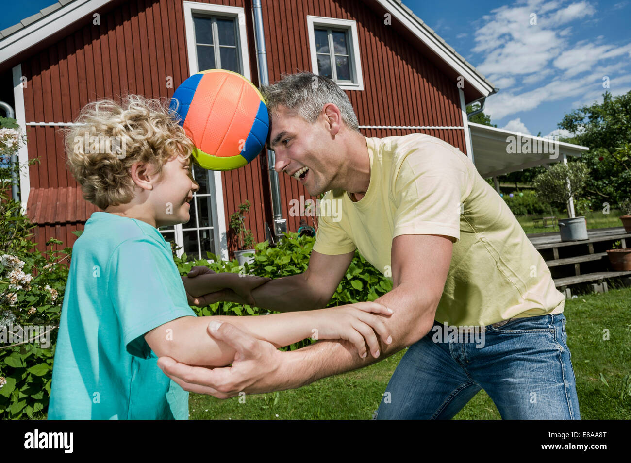 Father son balancing football playing fun garden - Stock Image