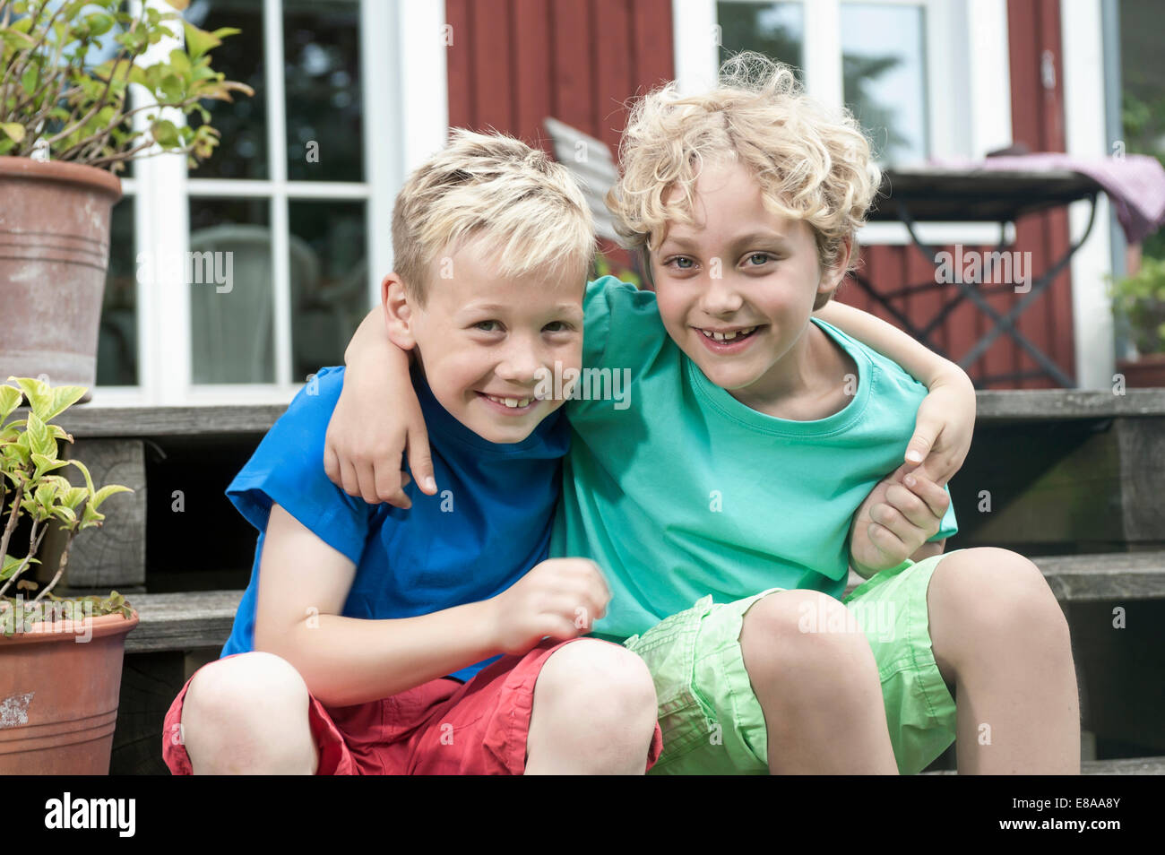 Friends young boys sitting steps house smiling Stock Photo