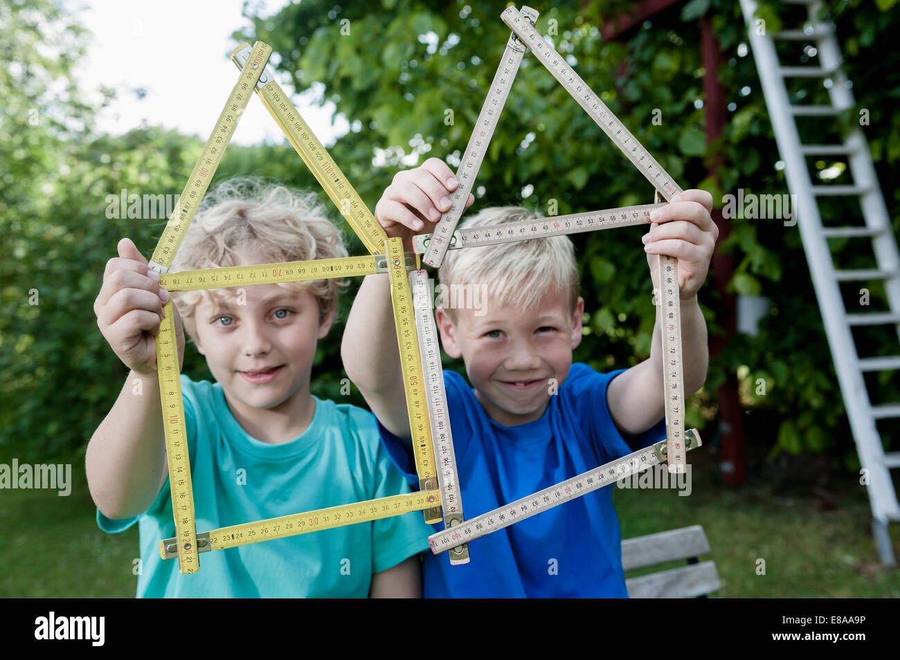 Close up two boys house shape ruler - Stock Image