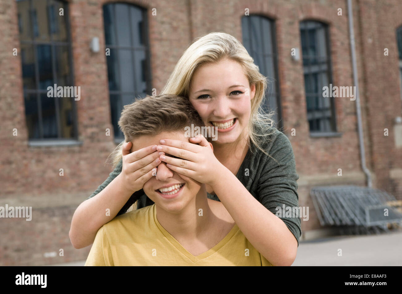 Portrait of teenage girl covering eyes of teenage boy, smiling - Stock Image