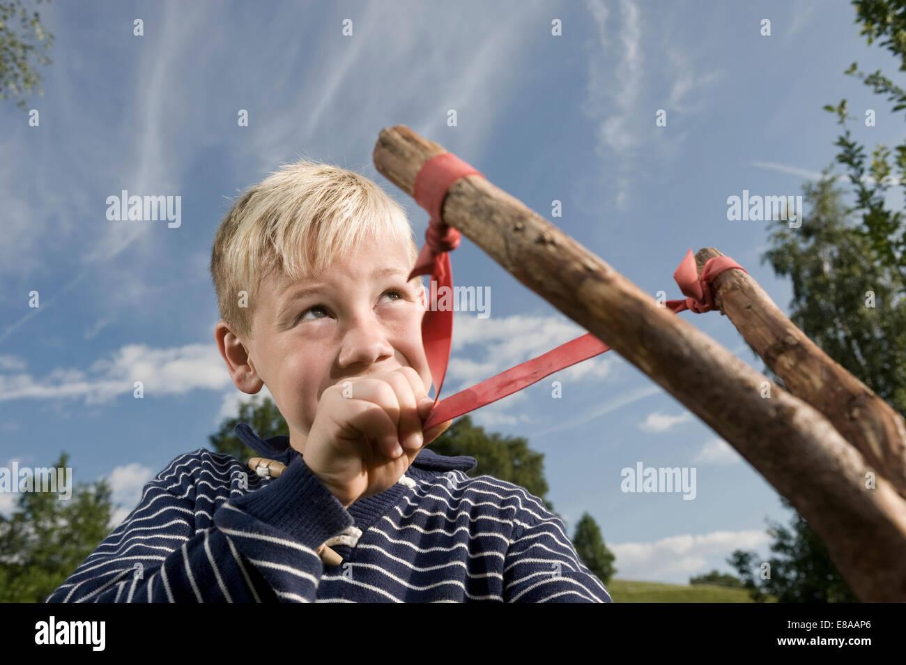 Boy aim slingshot sky holding portrait - Stock Image