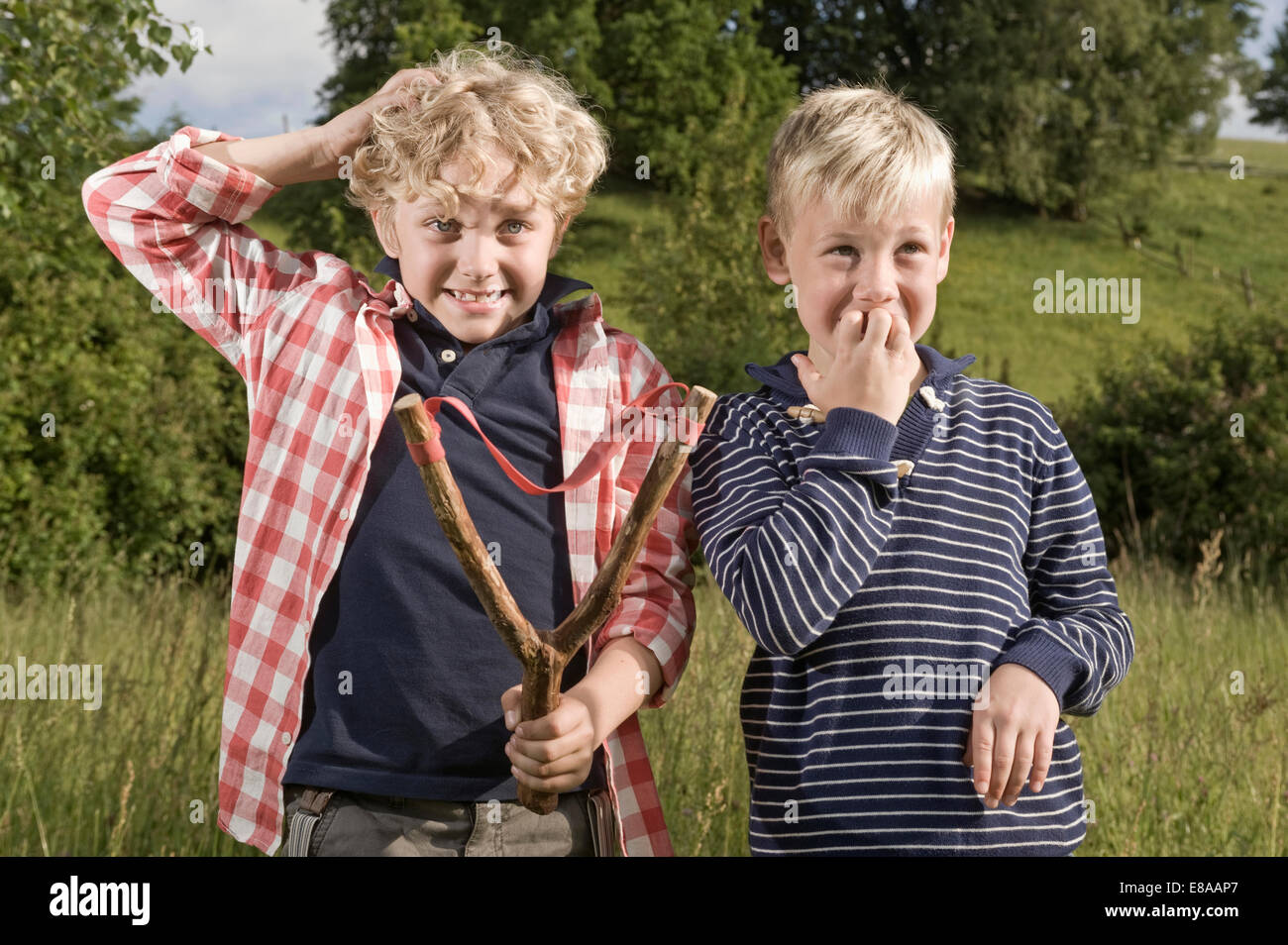 Young boys slingshot problem accident trouble - Stock Image