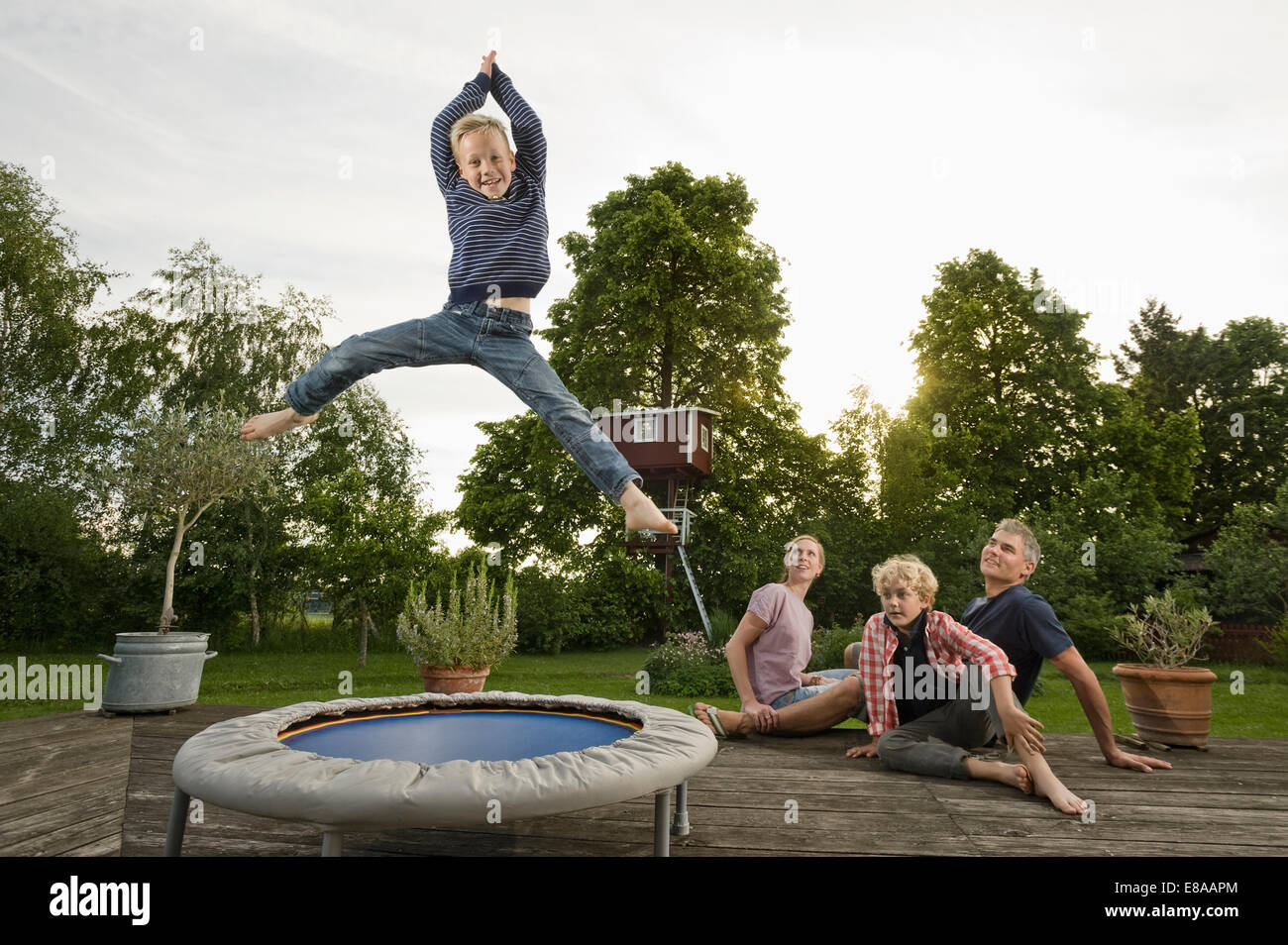 Young family garden boy jumping trampoline - Stock Image