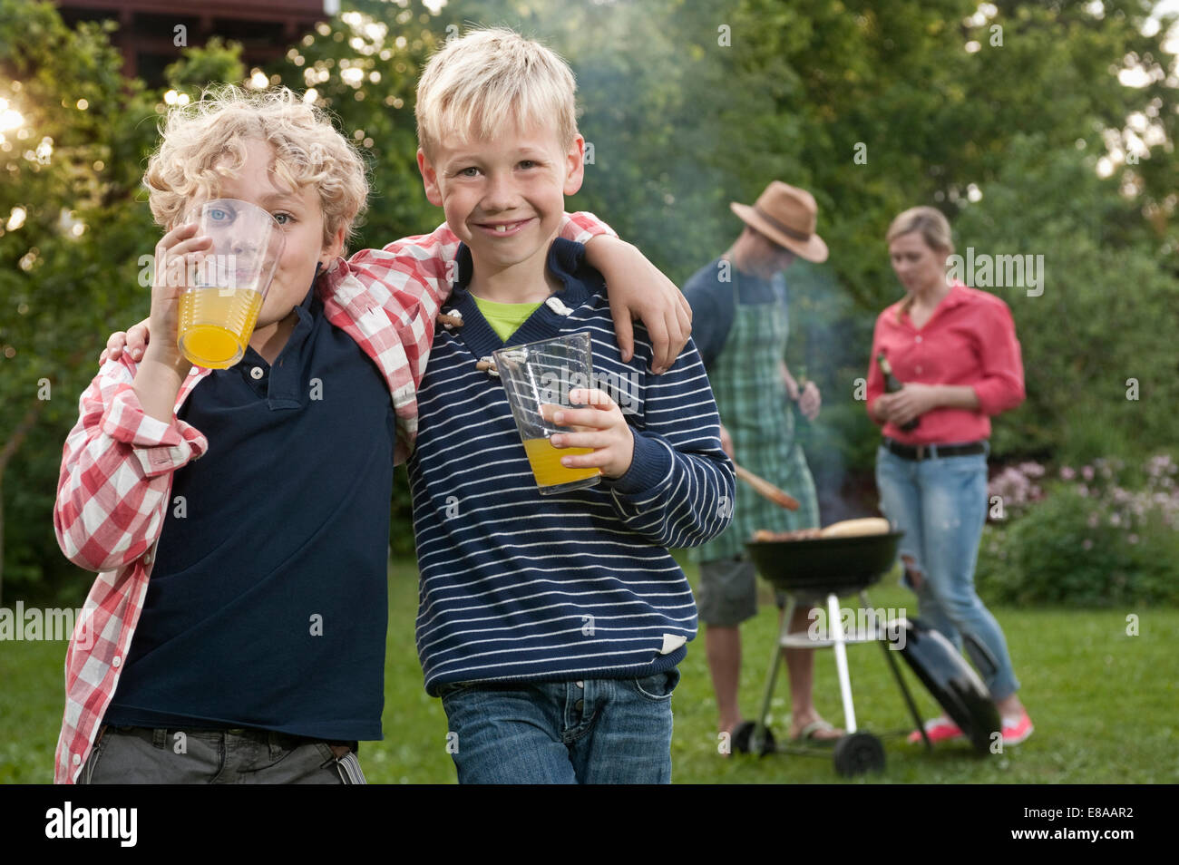 Family barbecue parents boys friends garden - Stock Image