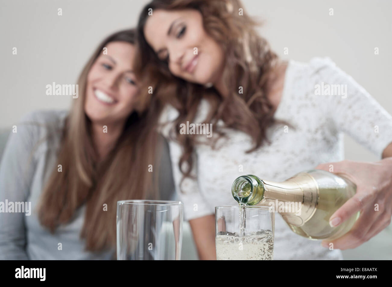 Young woman pouring champage into glasses while her female friend watching - Stock Image