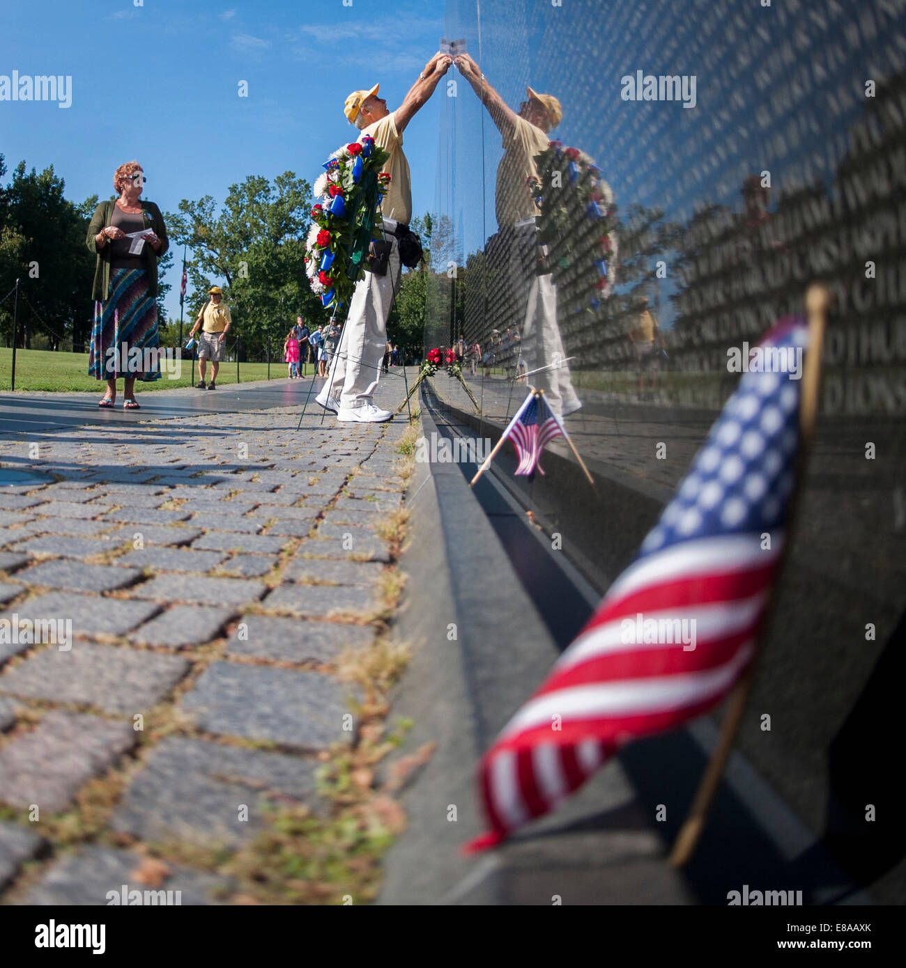 Karen McCaslin, left, observes a Vietnam Veterans Memorial docent makes a rubbing for her brother, U.S. Army Spc. - Stock Image
