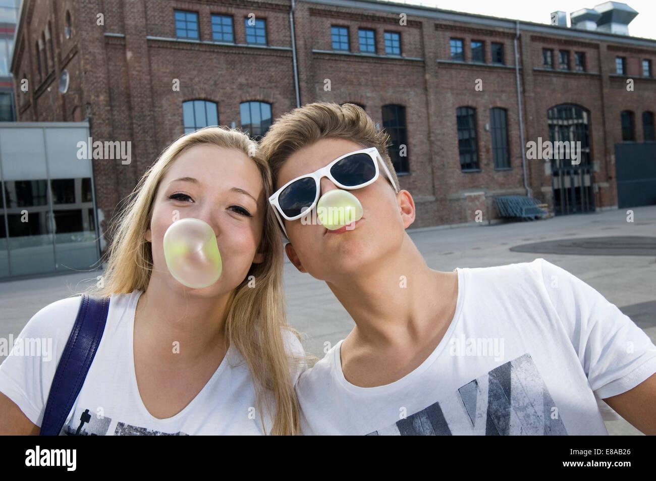 Teenage couple blowing bubble gum - Stock Image