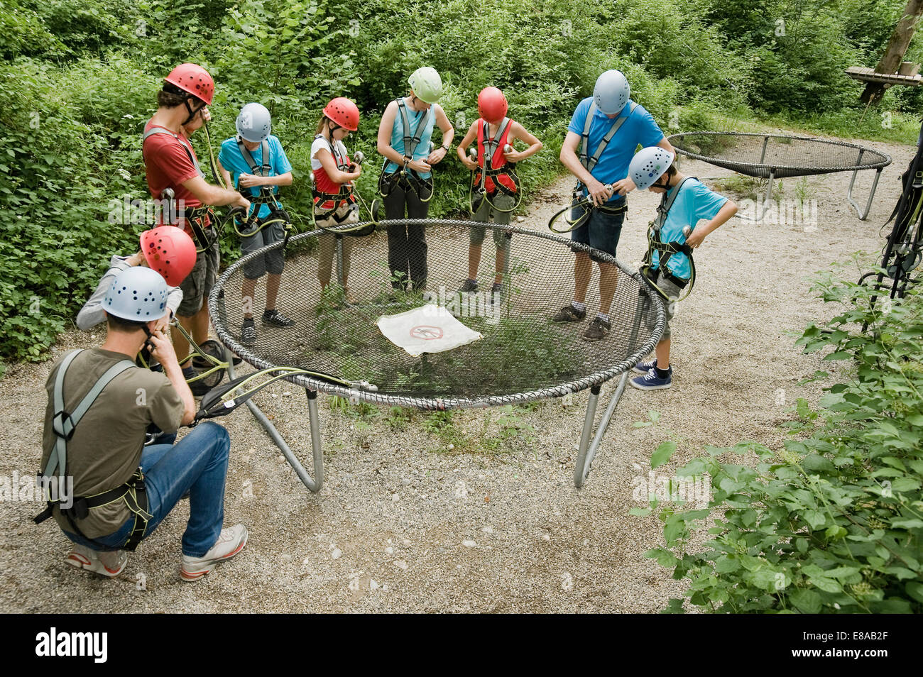 Young woman giving instruction to group of people for climbling crag - Stock Image