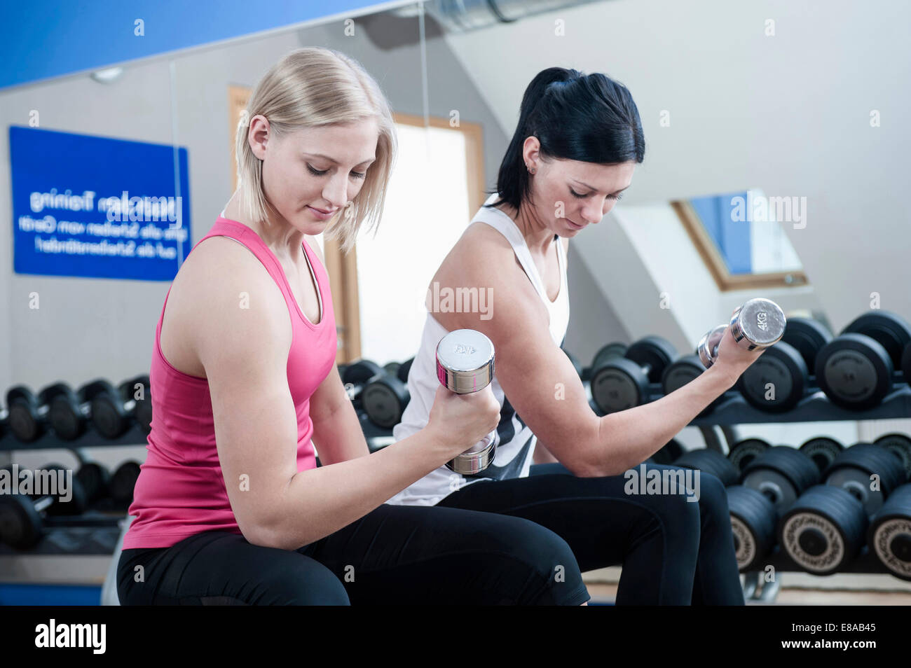 Two women in gym doing weight training - Stock Image