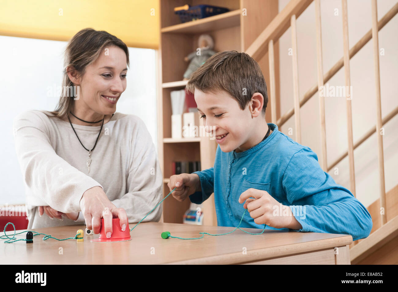 Portrait of playing boy and female childcare assistant - Stock Image