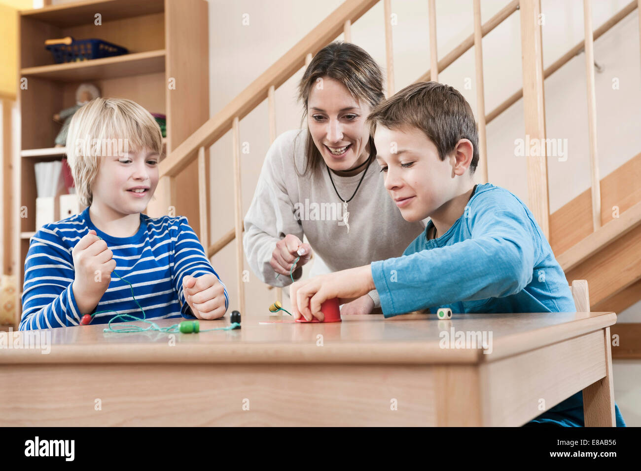 Portrait of two playing boys and female childcare assistant Stock Photo