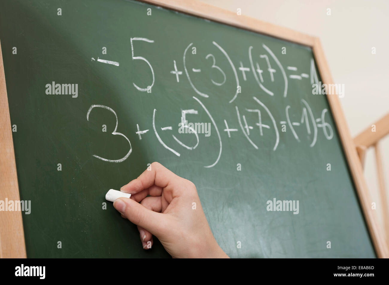 Girl writing arithmetic problem on blackboard - Stock Image