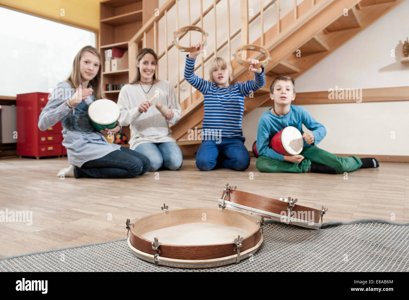 Group of female childcare assistant and three children drumming - Stock Image