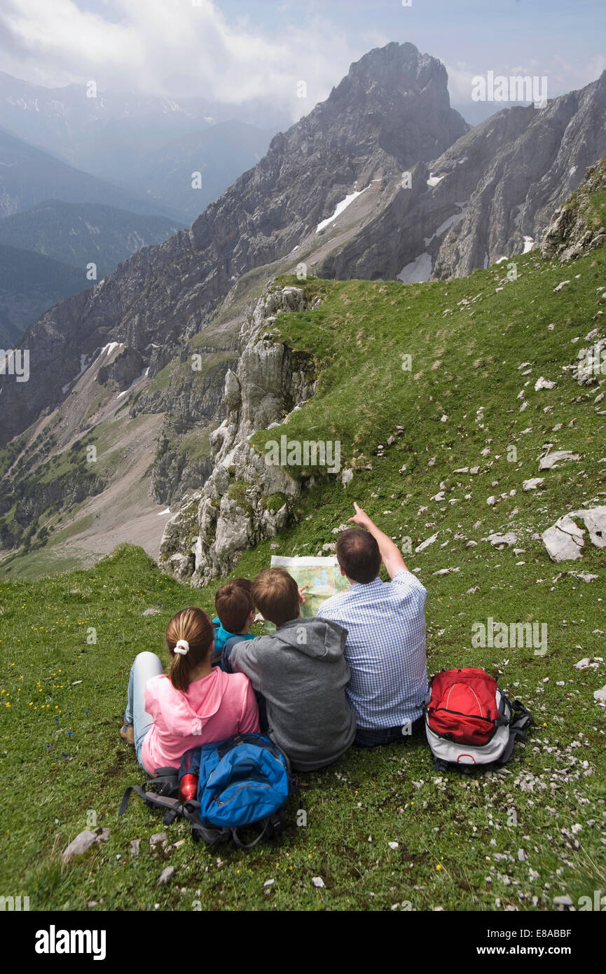 Father and kids looking at hiking map mountains - Stock Image
