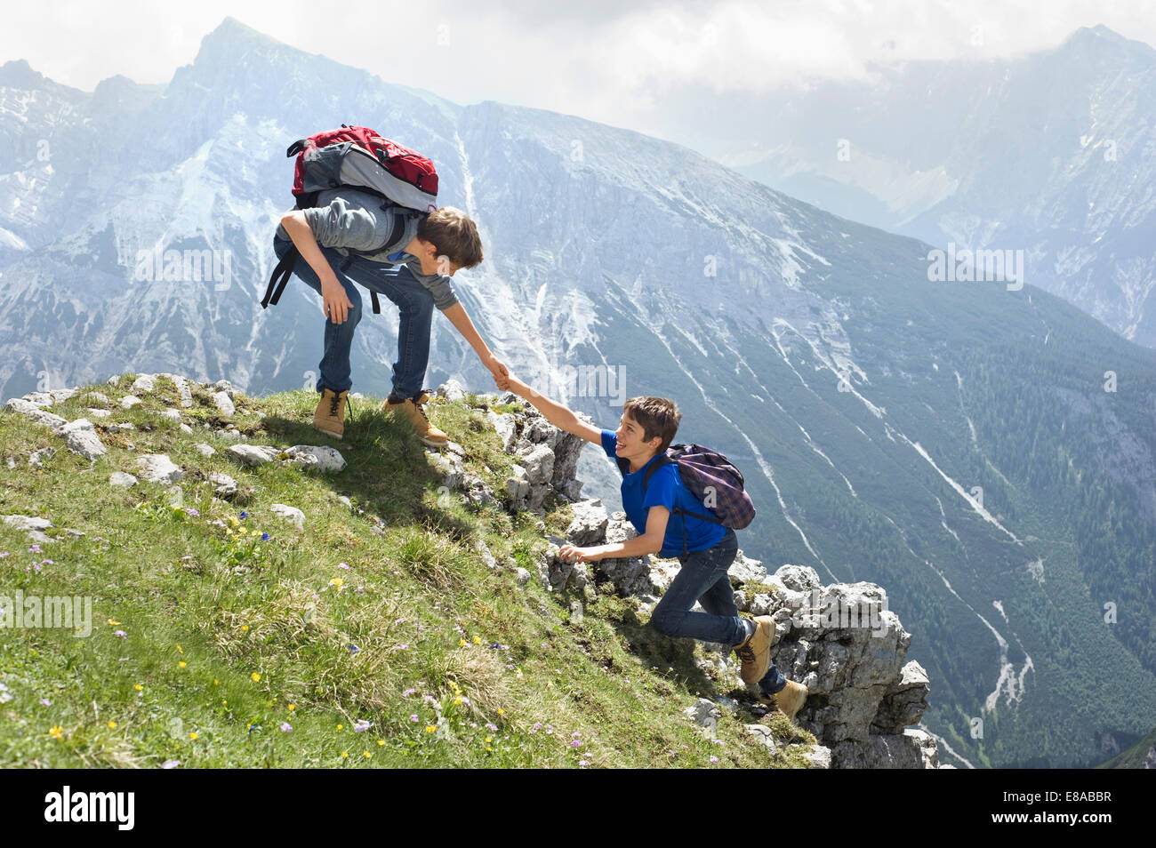 Teenage boys helping friend climbing in mountains - Stock Image