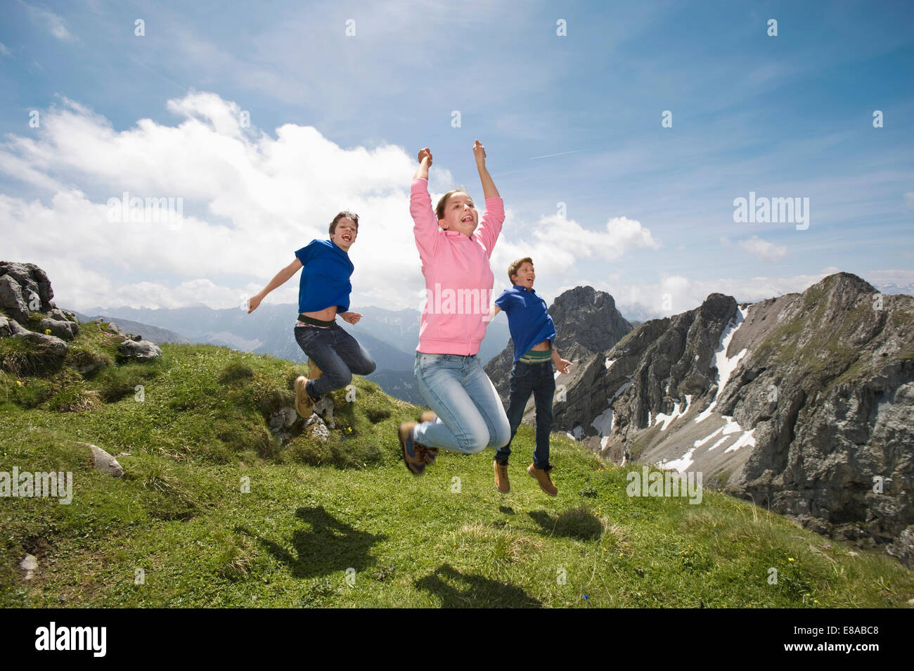 Girl and teenage boys jumping in air Alps Stock Photo