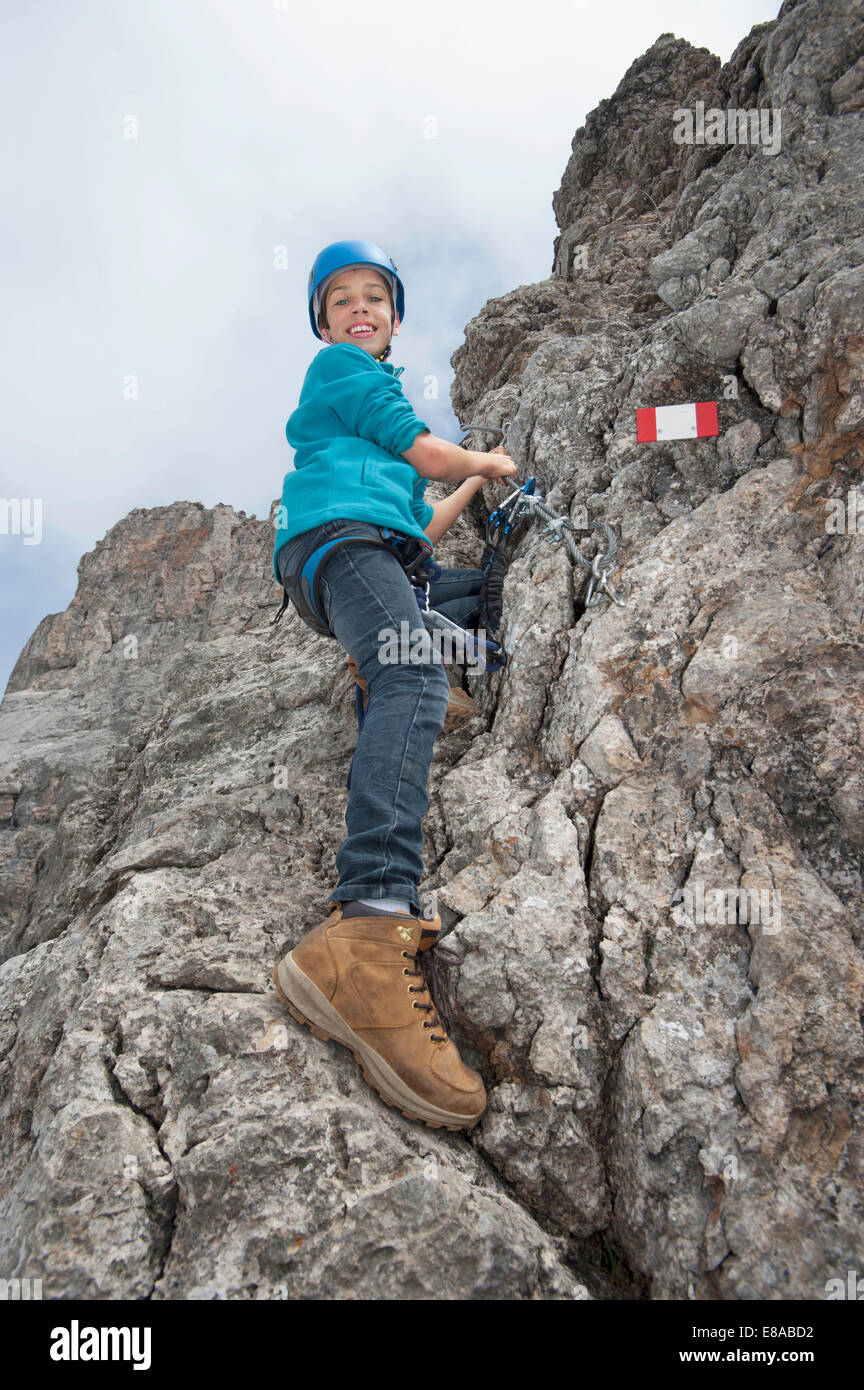 Young teenage boy holding rope on rock face - Stock Image