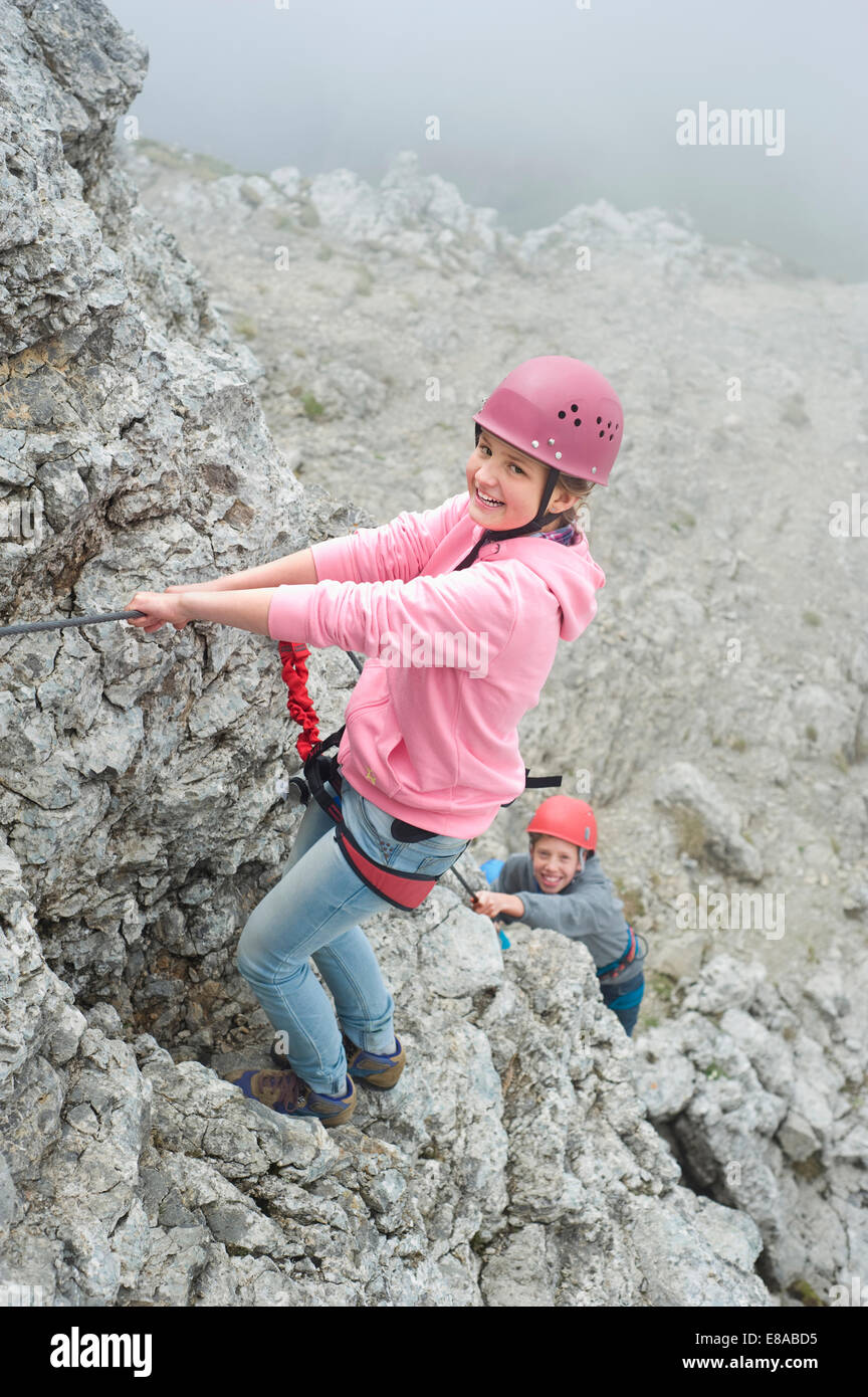 Brother sister climbing rock face mountains rope - Stock Image