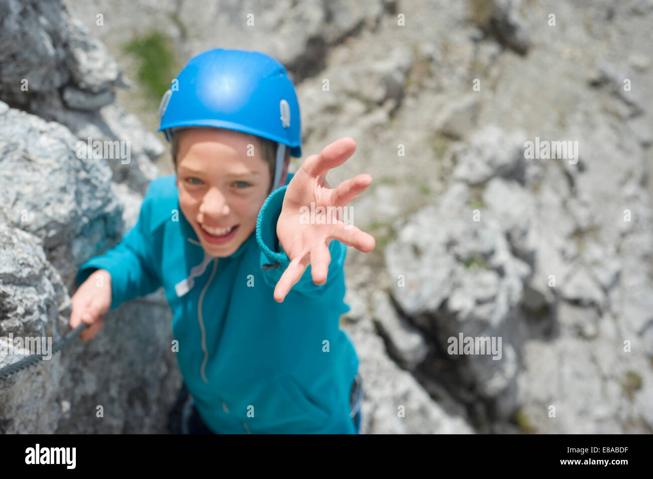 Teenager climbing Alps mountains reaching helping - Stock Image