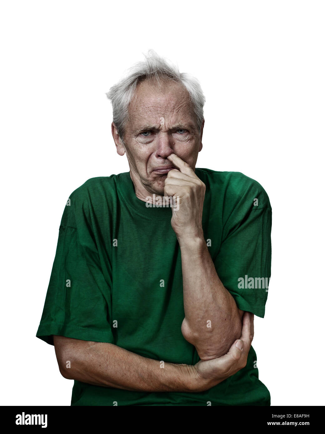 Mad looking senior male picks his nose. Grunge darkened portrait isolated on white background - Stock Image