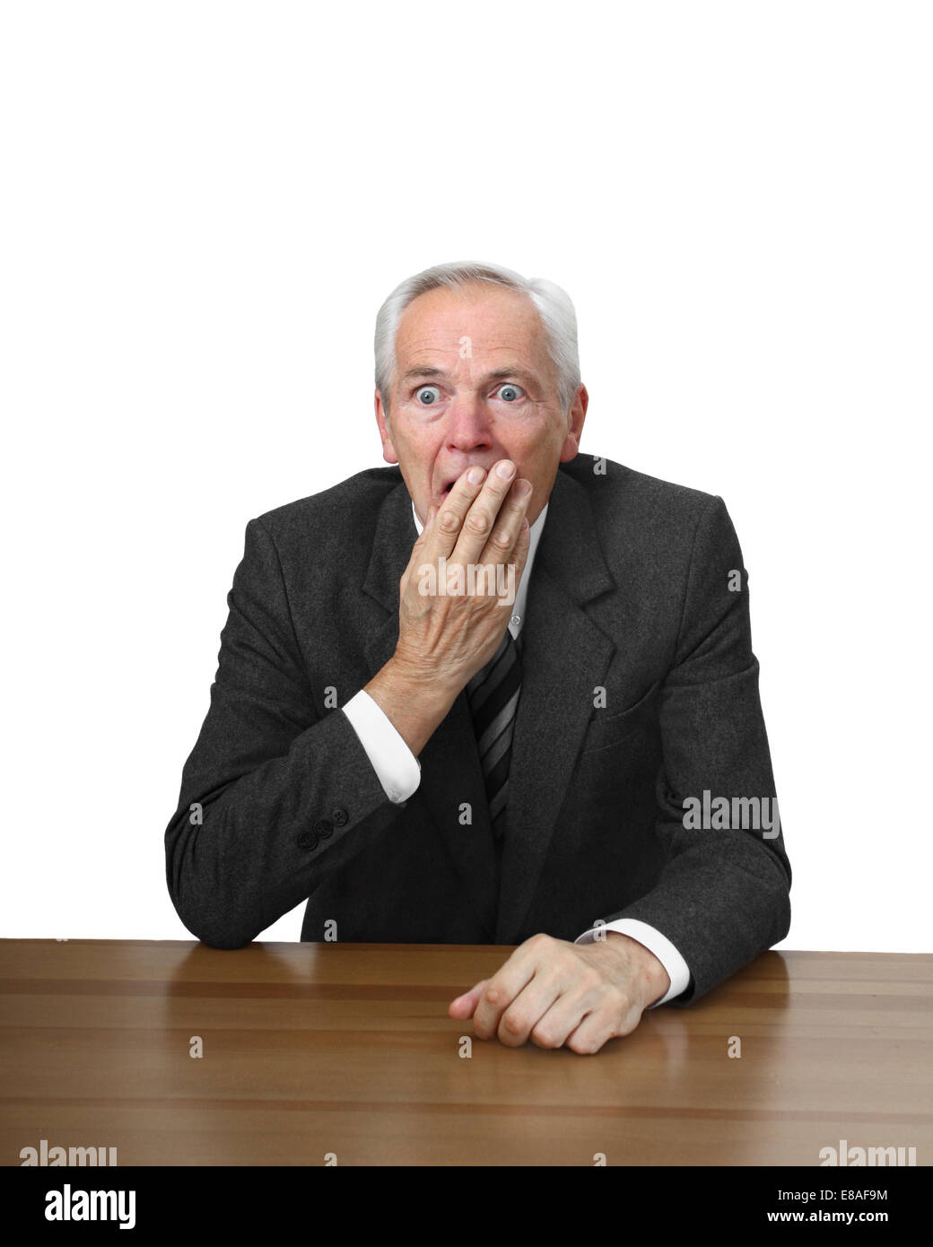 Shocked man sits at table covering her mouth by hand isolated on white background - Stock Image