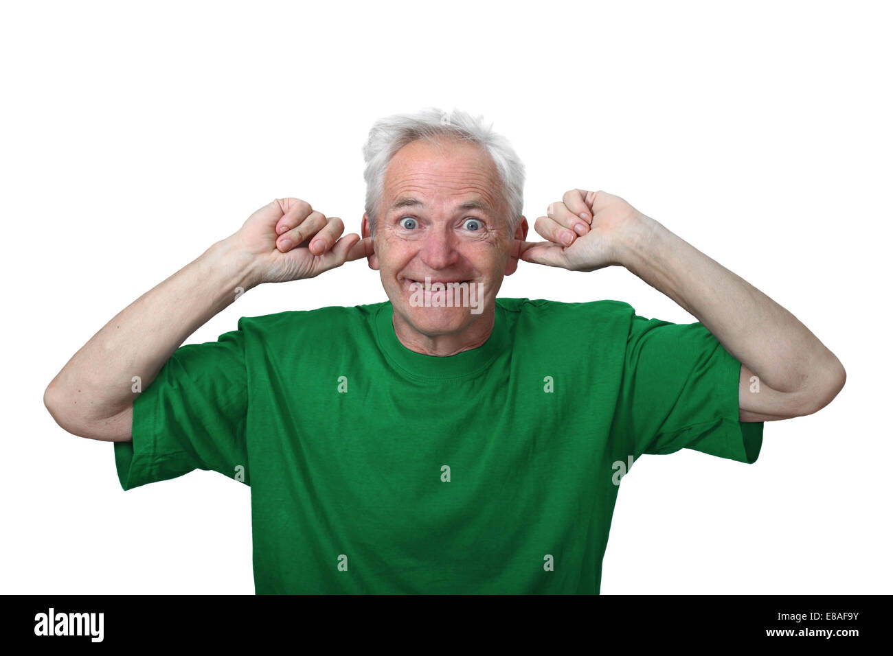 Senior man stuffed his ears with fingers and grins isolated on white background. Deaf and hears nothing - Stock Image