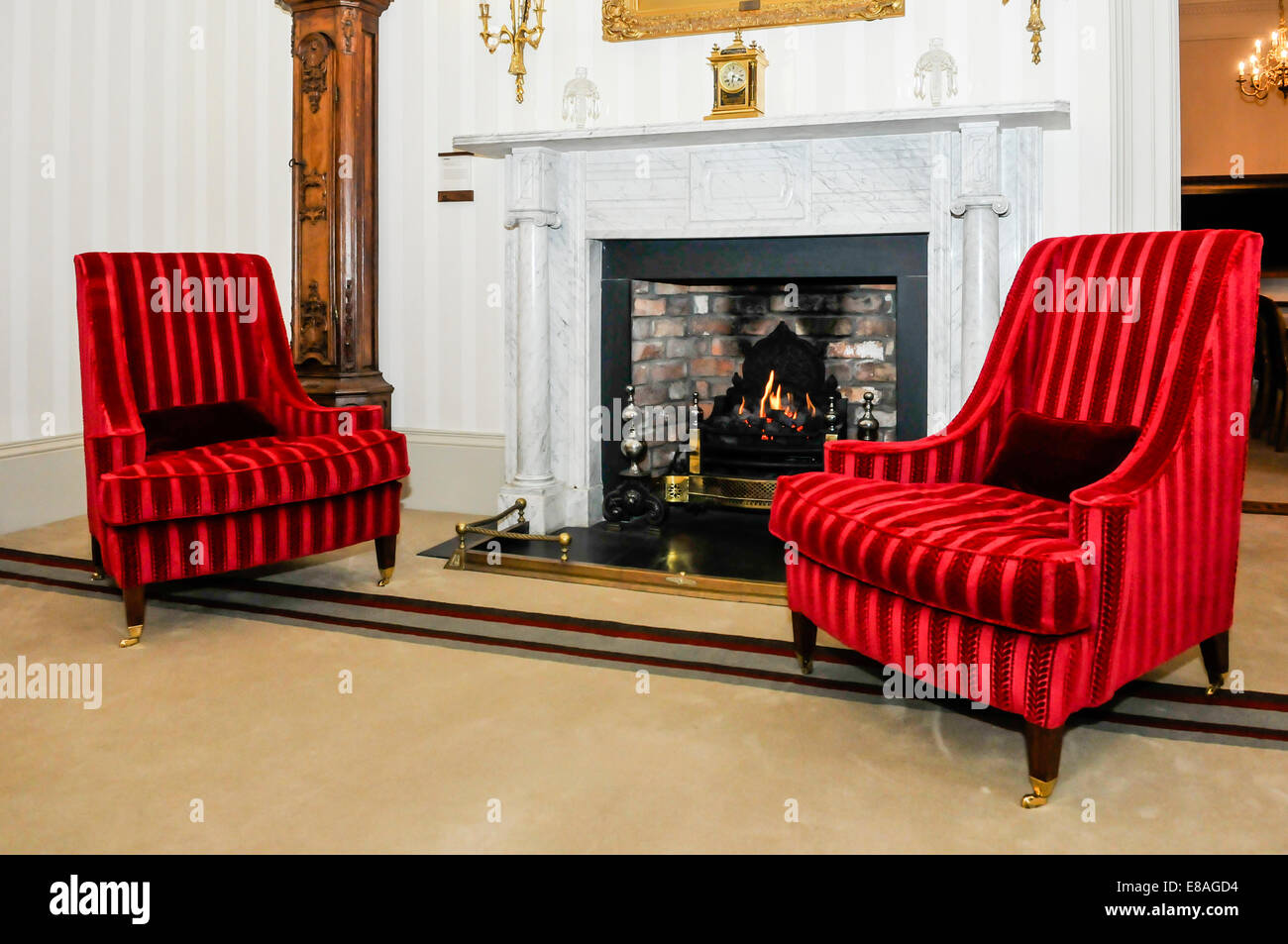 Two chairs beside a fireplace in a large, old fashioned house. - Stock Image