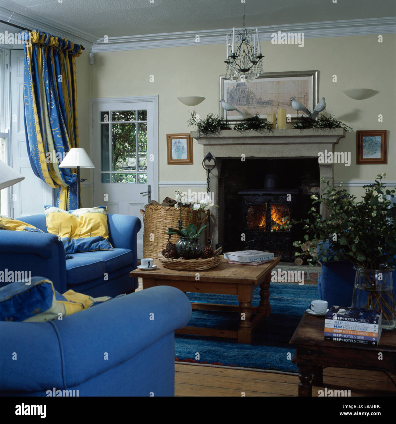 Blue sofas in country living room with wood-burning stove in stone ...