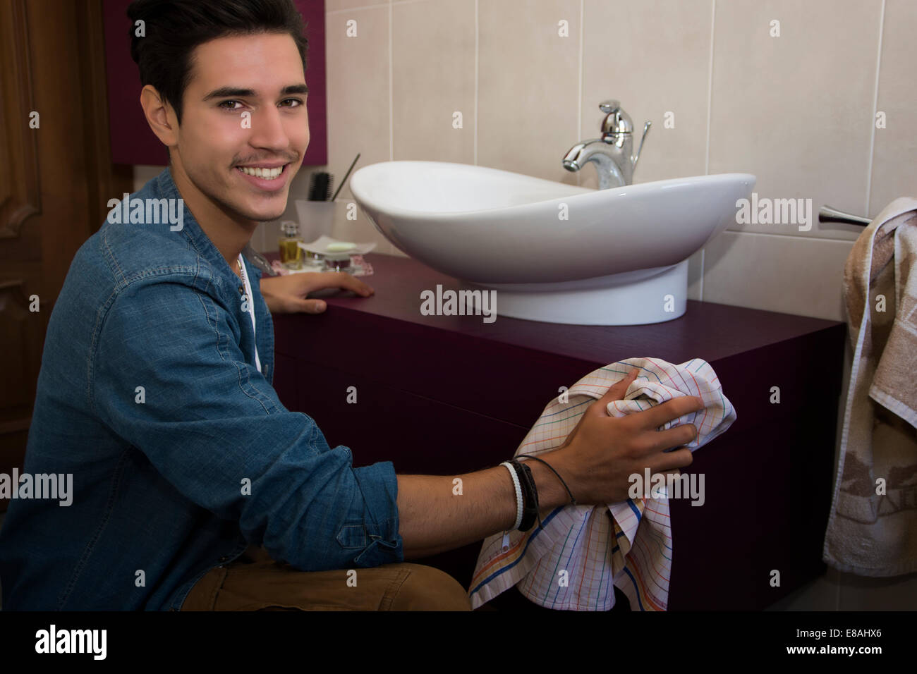 Cheerful young man kneeling down with a cloth in his hand cleaning the bathroom interior wiping the ceramic hand - Stock Image