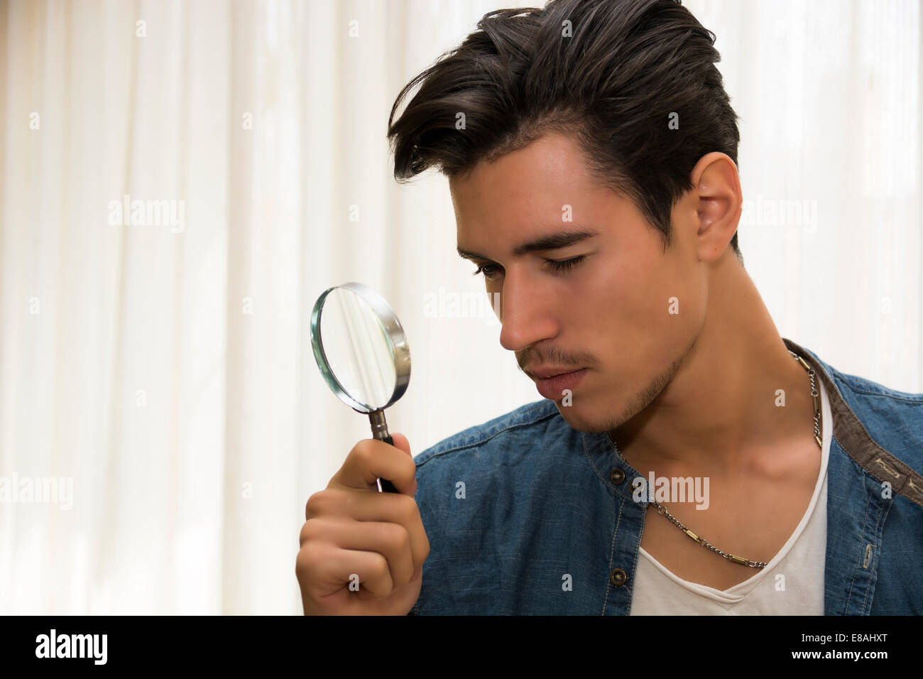 Young man looking through a magnifying glass in a conceptual image of a detective searching for clues, inspection, - Stock Image