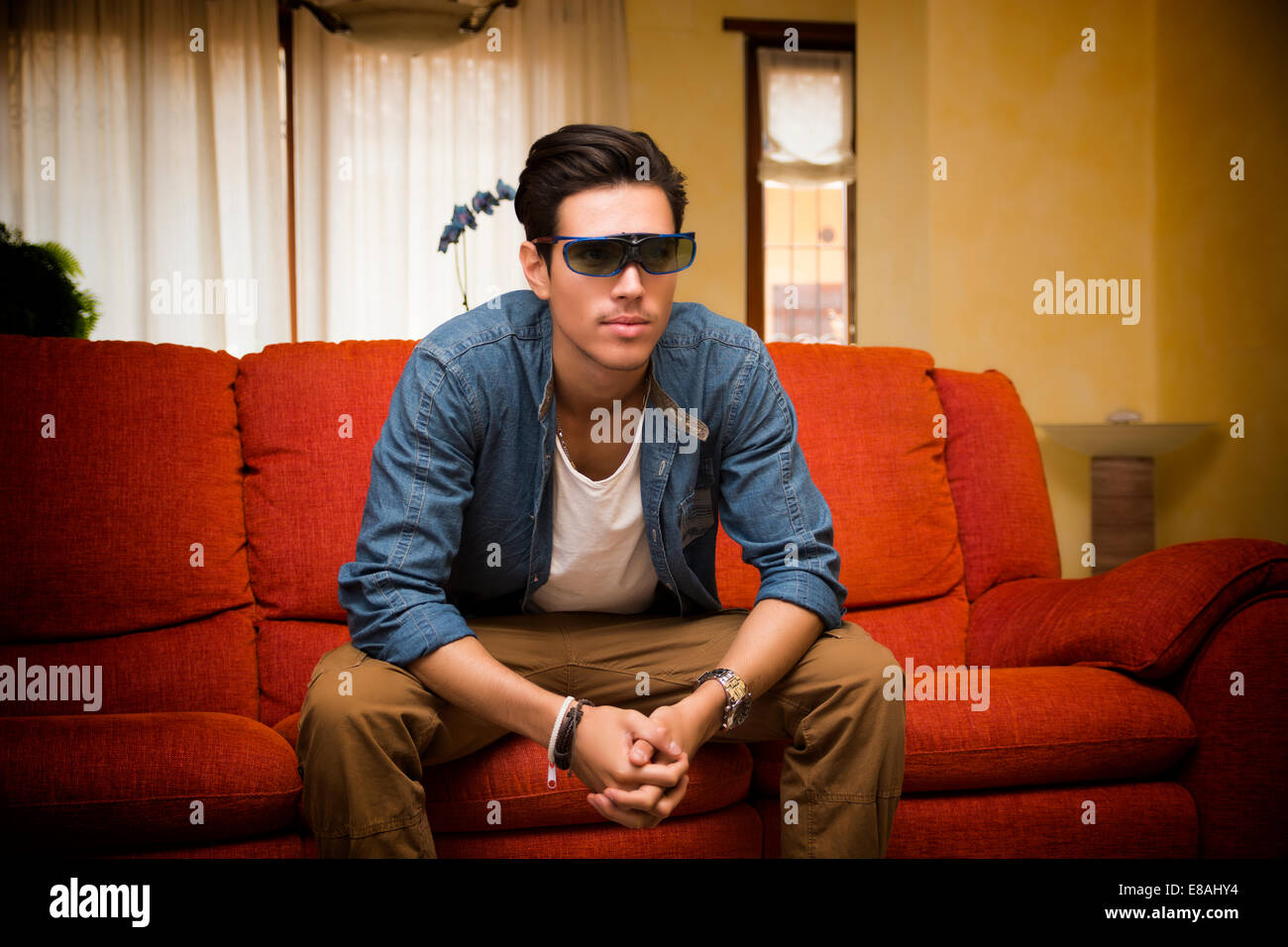Young man in 3d glasses sitting on a sofa in the living room watching reality television leaning forwards with an Stock Photo