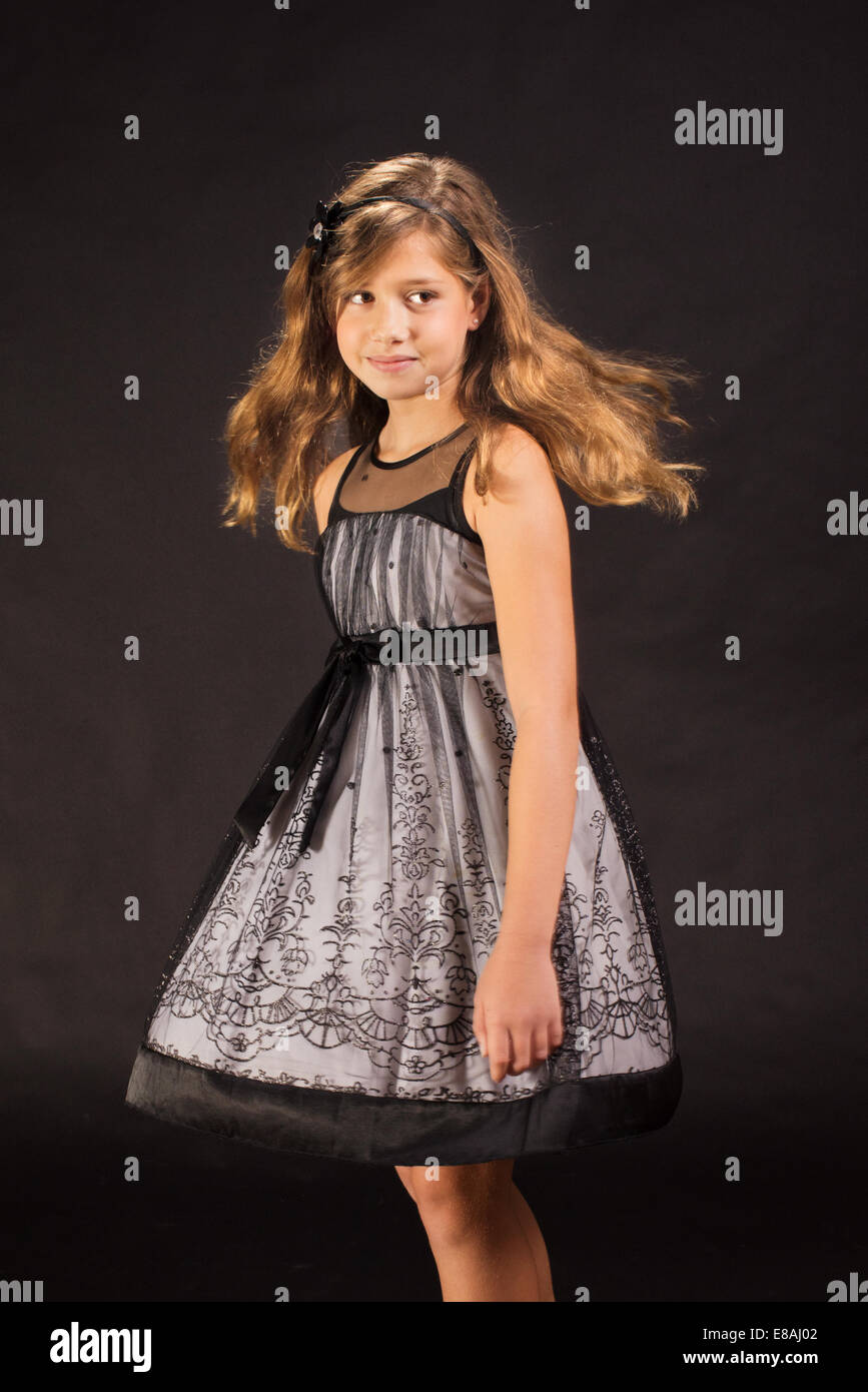 Young girl with long hair twirling in gorgeous dress. - Stock Image